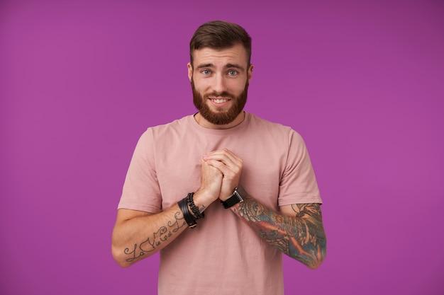 Pietoso attraente brunetta uomo con barba e tatuaggi piegando le mani alzate in gesto di accattonaggio, fronte rugosa e sorridente ampiamente, isolato su viola
