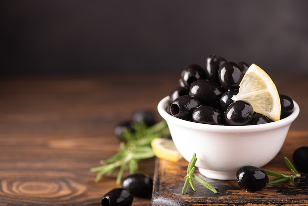 Pitted black olives with lemon in a white bowl, close up
