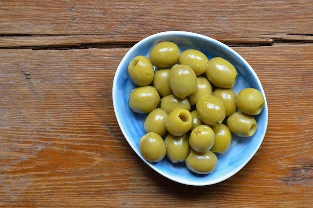 풍된 나무 테이블 위에 파란색 접시에 움푹 된 녹색 올리브; 올리브에 집중