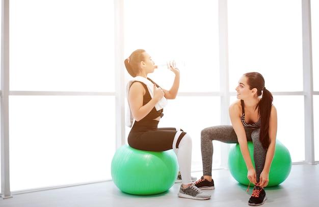 緑のfitballsに座って休憩している2人の若い女性の写真
