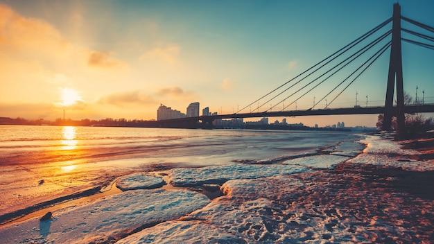 Pivnichnyi bridge silhouette over half frozen dnipro river