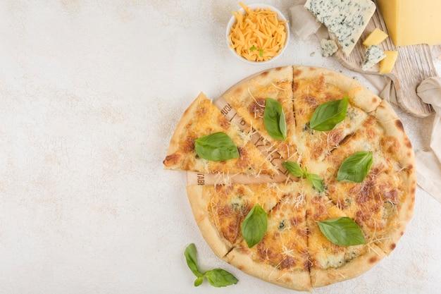 シーザーソース、チェダーチーズ、マーブルチーズ、パルメザンチーズ、モッツァレラチーズ、オリーブを背景にしたピザ4チーズ。テキストのコピースペースを含む上面図。クラシックなイタリア料理。