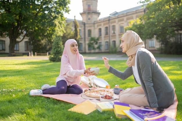 피자와 과일. 함께 공부 한 후 밖에서 피자와 과일을 먹고 히잡을 입은 학생들