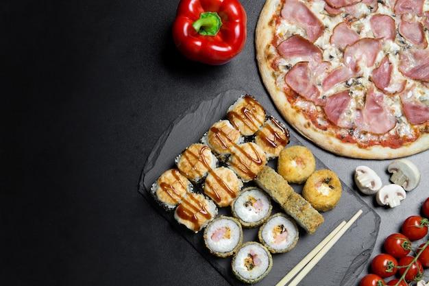 Пицца и суши-роллы на доске