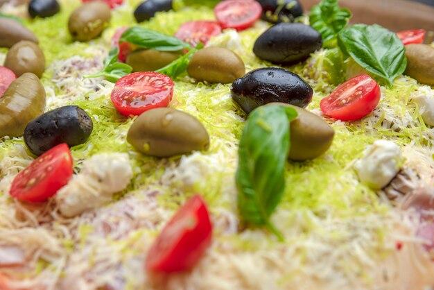 ピザの背景。ピザのクローズアップ、上面図。チェリートマト、カラフルなチーズ、オリーブを使った生ピザ。