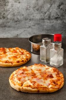 핫도그와 치즈를 곁들인 피자 베이컨 햄 모형 조미료는 소금 오레가노와 파프리카입니다.
