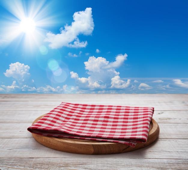 피자 보드와 나무 책상 관점에 냅킨. 하늘과 태양 여름 배경입니다.