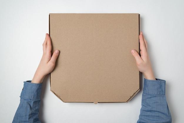 白い背景の上の子供の手の中のピザの箱。上面図。スペースをコピーします。