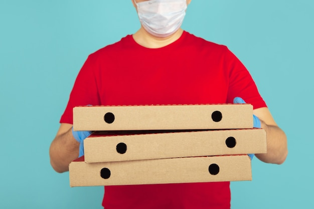 Pizza boxes for delivery. man courier in gloves.