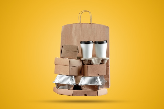 Pizza boxes and food delivery paper bag with a disposable cup of coffee and a wok box on a yellow background