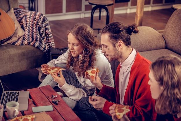 ピザブレイク。自宅で彼女の兄弟とピザ休憩を楽しんでいる巻き毛の楽しい魅力的な10代の少女