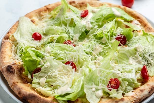 チキン、パルメザンチーズ、卵、チェリートマト、フレッシュレタスのピザシーザー、上面図。