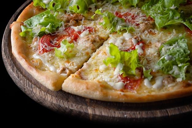 Пицца цезарь, с курицей, помидорами, сыром, зеленью, на деревянной доске, частично сфотографировано