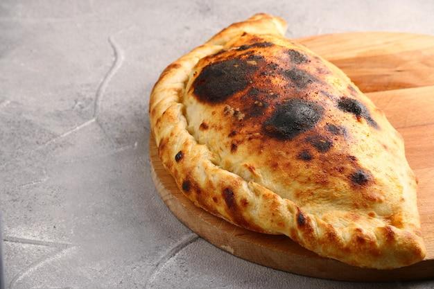 木の板にピザ カルツォーネのクローズ アップ。灰色のコンクリート テーブルの上の半分のピザに折ります。ピザのコンセプト。