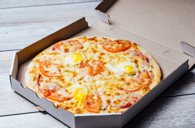 Pizza in a cardboard box against a grey wood