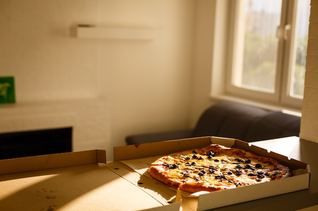 Pizza in cardboard box on table