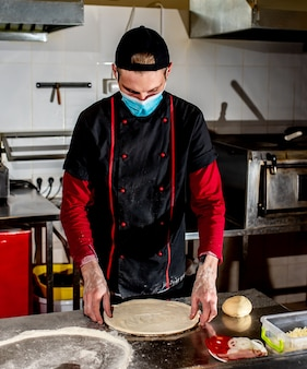 Pizza chef or maker in a medical mask against coronavirus, makes pizza dough blanks. pizza dough making concept
