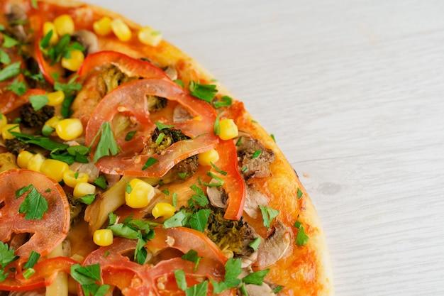 白い木の表面のピザのクローズアップ。家にいる人へのフードデリバリー
