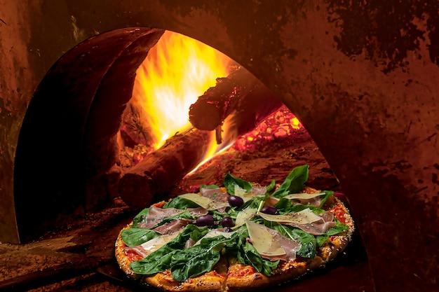 Пицца выходит из дровяной печи. вкус: моцарелла, пармская ветчина, сыр пармезан, руккола, маслины с орегано и кунжутной каймой. бразильская кухня