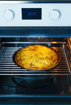 가스 오븐의 둥근 쟁반에 피자 요리. 오븐의 둥근 쟁반에 치즈를 얹은 피자. 수제.
