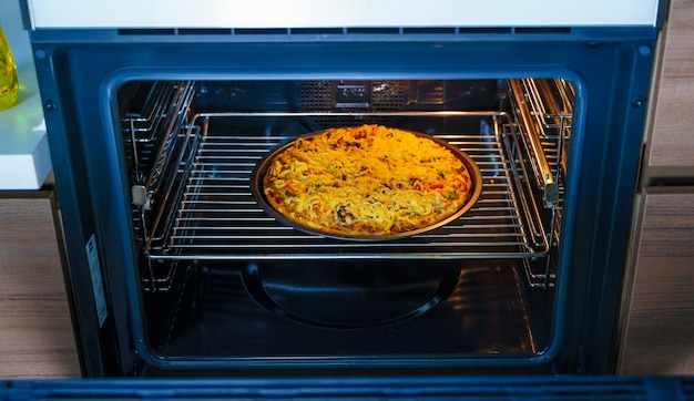 오븐의 둥근 쟁반에 피자 요리. 수제 피자.