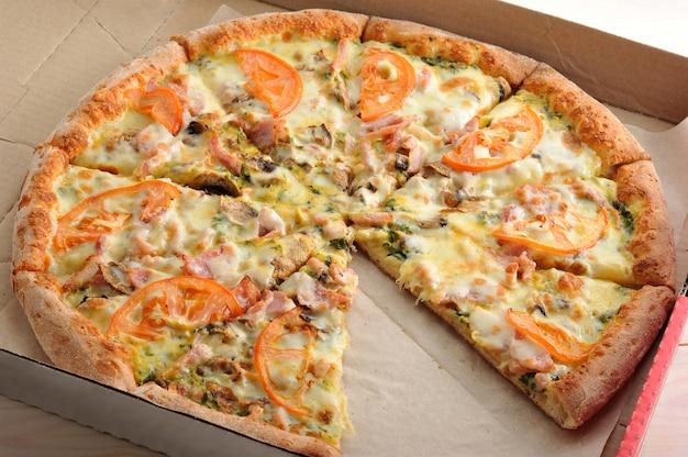 Пиццу нарезать ломтиками с грибами, помидорами, сыром и беконом