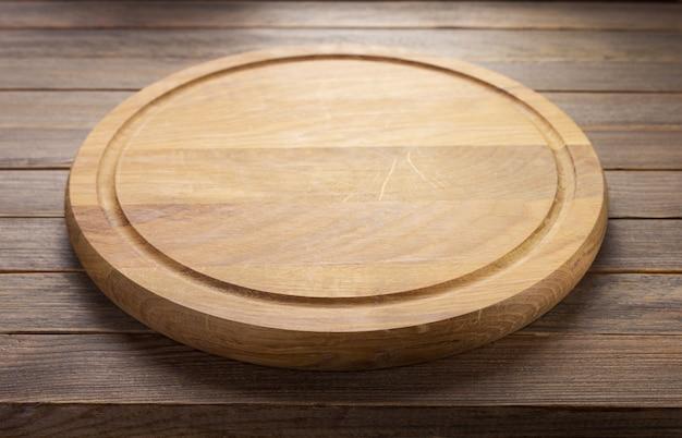 소박한 나무 테이블 판자 배경의 피자 커팅 보드, 전면 보기