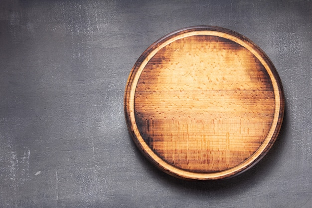 Pizza cutting board at  table or wall, with stone background texture