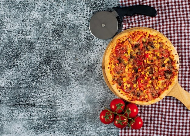 Pizza in a cutting board with tomatoes, pizza cutter top view on a gray stucco and picnic cloth background