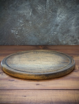 Pizza cutting board at wooden table, with wall background texture