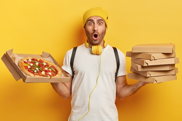 Pizza dealer holds carton boxes with snack, looks with omg expression, wears yellow hat and white t shirt, impressed by something, has much work