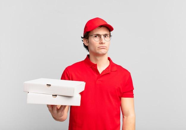 Мальчик, доставивший пиццу, грустит, расстроен или зол, смотрит в сторону с негативным отношением и хмурится в знак несогласия.