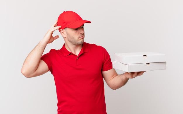 피자 배달 남자는 어리둥절하고 혼란스러워 머리를 긁적이며 옆을 바라보고 있다