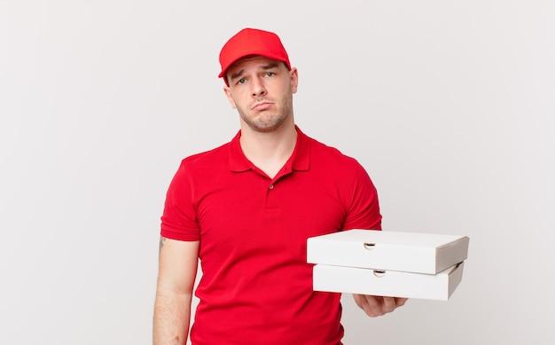 ピザは、不幸な表情で悲しみと泣き言を感じ、否定的で欲求不満の態度で泣いている男性を届けます