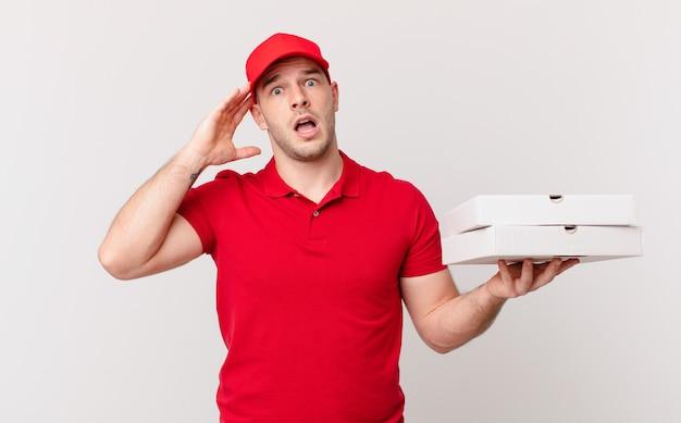 ピザは、幸せそうに見え、驚き、驚き、笑顔で、驚くべき信じられないほどの良いニュースを実現する男性を届けます
