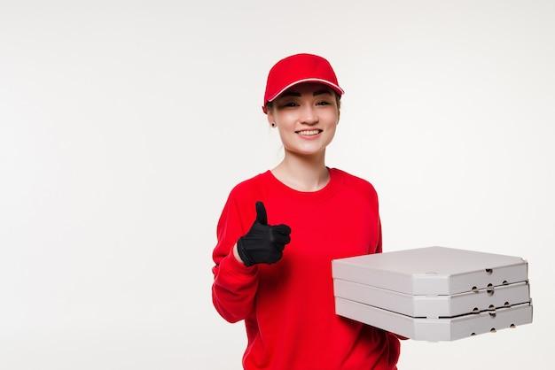 Donna asiatica di consegna della pizza con i pollici in su che tiene una pizza sopra isolata su bianco