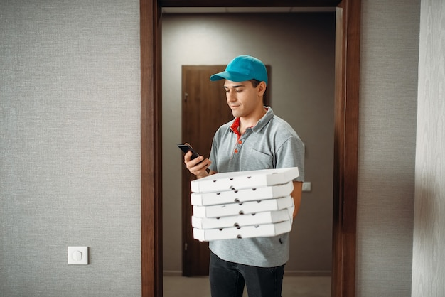 Pizza delivery boy in t-shirt and cap calls to customer