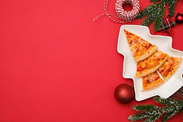 Pizza delivery for christmas concept. edible christmas tree made from pizza margarita on red background with decorations