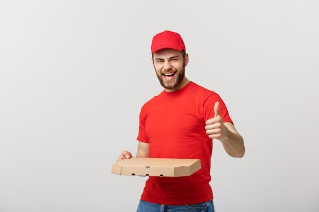 Концепция доставки пиццы. молодой красивый работник доставляющий покупки на дом показывая коробку пиццы и держа большой палец руки вверх по знаку.