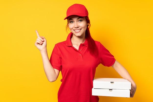 幸せと上向きの孤立した背景の上にピザをかざすピザ配達の少女