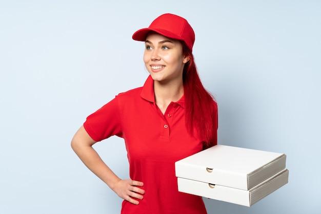 腰に腕と笑顔でポーズをとって孤立した背景の上にピザを保持しているピザ配達の女の子