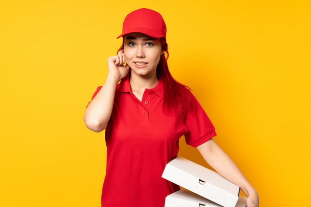 Девушка доставки пиццы держит пиццу над изолированной стеной, расстроена и закрывает уши