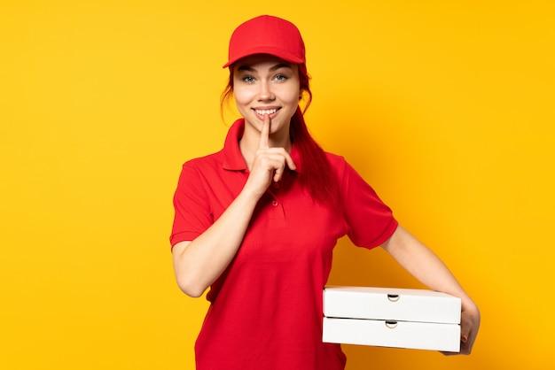 Девушка доставки пиццы держит пиццу над изолированной стеной, показывая знак жеста молчания, положив палец в рот