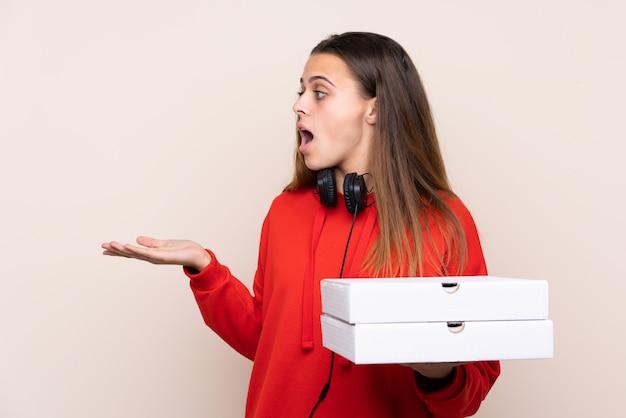 驚きの表情で孤立した壁にピザを置くピザ配達の少女