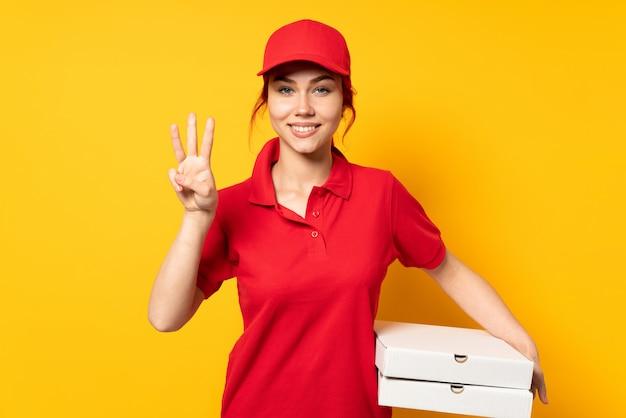 Девушка с доставкой пиццы держит пиццу над стеной счастливой и считает три пальца
