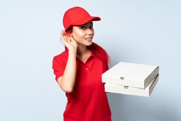Девушка по доставке пиццы держит пиццу за стеной, слушая что-то, положив руку на ухо