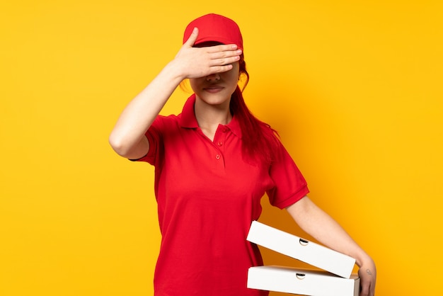 Pizza delivery girl holding a pizza over isolated covering eyes by hands. do not want to see something