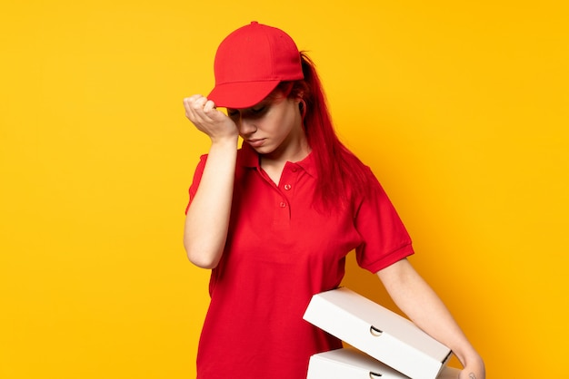Pizza delivery girl holding a pizza over isolated wall with headache