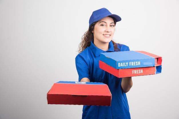 흰색 바탕에 세 개의 상자를 들고 피자 배달 소녀. 고품질 사진