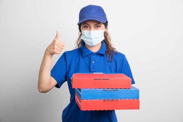 Доставка пиццы держит три коробки с медицинской маской и показывает палец вверх на белом